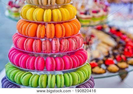 macaron. Delicious french macarons colorful multilevel pyramid and sweet cake dessert on plates or stands on blurred background. Food dieting. Birthday anniversary wedding celebration