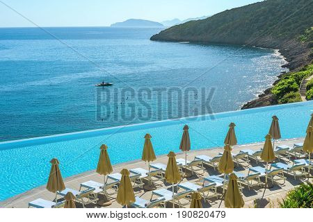 Scenic landscape with a sun deck and a swimming pool on the background of the sea bay of Crete Greece