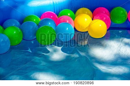 Many colored balls swim in a small pool