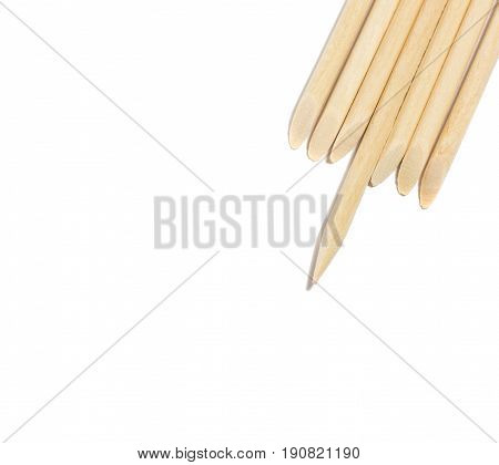 Disposable thin sticks for manicure on a white background they are made of orange wood and have two different tips flat and sharp