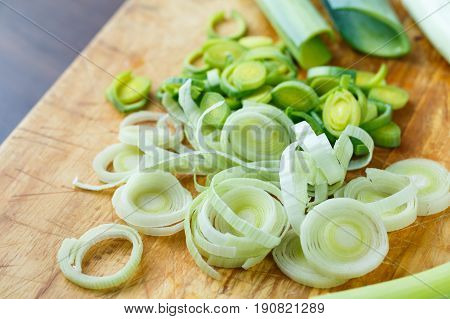 Fresh Leek Cut Into Small Pieces On Wooden Board