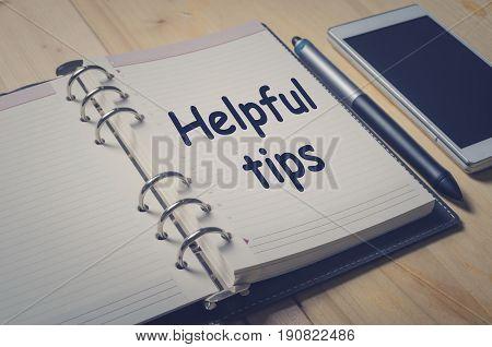 Helpful tips message on notebook with pen and smart phone on wooden table