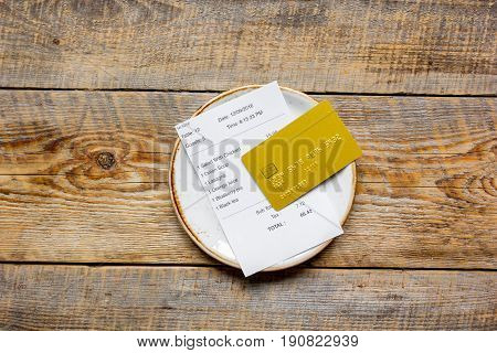 Plate And Receipt Bill For Payment By Credit Card Wooden Table Background Top View