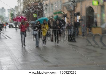 Abstract city street seen through raindrops on window glass. Girls in colorful clothes under umbrellas walking down the street, blurred background. Concept of modern youth, seasons, weather