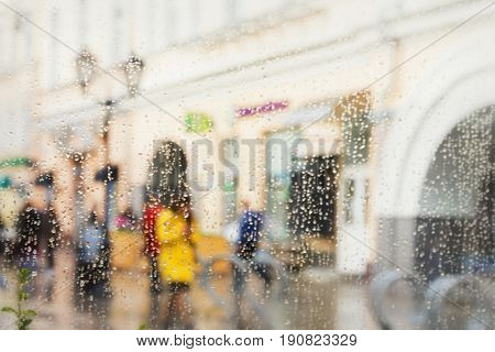 Abstract blurred silhouettes of people after rain in the city, girl in yellow seen through raindrops on window glass, blurred background, backdrop, wallpaper or banner design. Concept of spring weather, seasons, modern city.