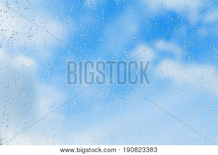 Textured blue background of sky with natural water drops on window glass, rain texture. Concept of clear, pure, bright, renovated. With place for your text. Modern background, pattern, wallpaper