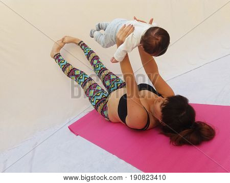Mum and two months old baby boy training  together, mum and baby gym