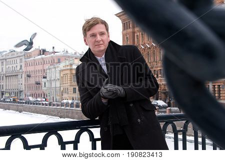 Male In Winter On Bridge In A Coat And Gloves