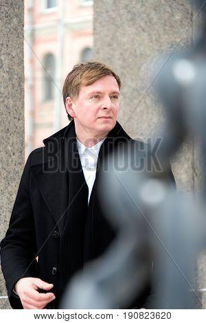 Male Adult In Black Coat On The Bridge In Winter
