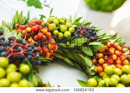 Details of a beautiful bright floral wreath with berries. Decorations for decorating a holiday, a bouquet of a bride, decorating events. Close-up and soft focus.