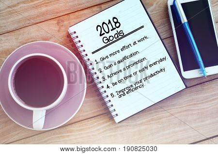2018 Goals List On Note Pad, Wood Table With Coffee, Pen And Smart Phone Retro Styled.
