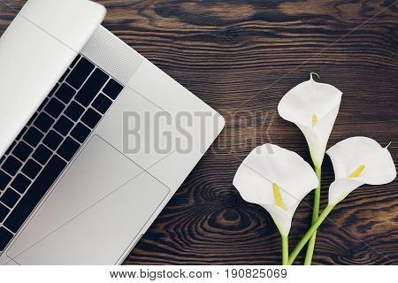 flat lay white calla flowers and a laptop on a wooden background, top view.