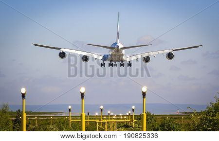 A380 plane landing at Manchester Airport over Runway Lights