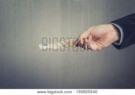 Businessman`s hand holding a 5o euro banknote. Paying buying or selling concept.