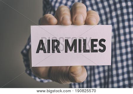Businessman shows AIR MILES card. Travel and vacation concept.