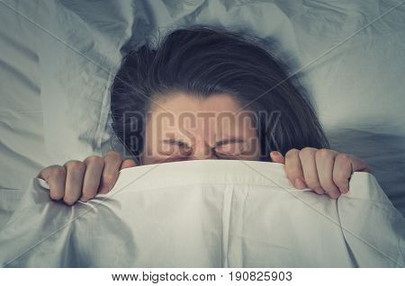 Woman with stressed face expression eyes closed hiding behind sheet in bed. Avoiding responsibility concept.