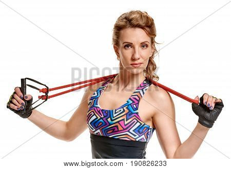 Portrait of beautiful fitness woman training with stretching expander