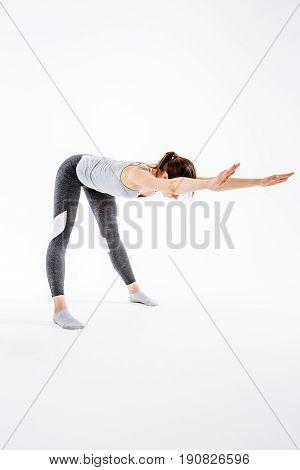 Young girl doing yoga on isolated background