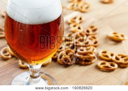 Beer glass pint with brezel. Traditional german Oktoberfest drink and food on wooden background