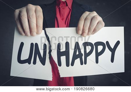 Businessman tearing up a sign saying - Unhappy - conceptual image of positive attitude and transformation.