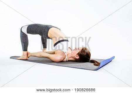 Young woman practicing on gray mat at empty white background