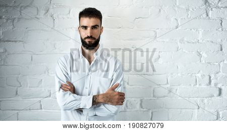 Full body portrait of smiling young casual bearded man standing against white brick wall, arms crossed, copyspace.