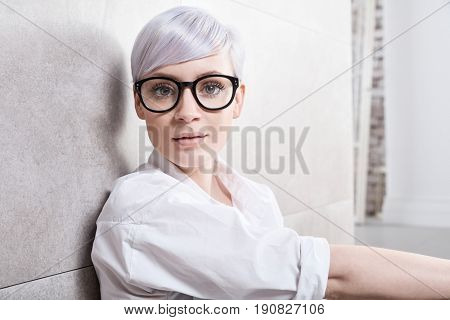 Closeup portrait of young wise woman looking at camera in glasses.