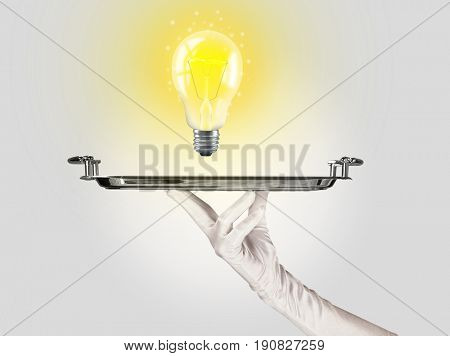 Serving a bright business idea concept using a bulb with bright sparkling warm yellow light presented on a silver plate
