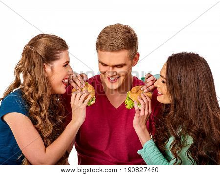Group hamburger fast food with ham in people hands . Fast food concept. Man and women on eating party. Girls fool around and feed man. Guy on date with two girls at same time.