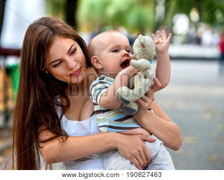 Baby in park outdoor. Kid with toy on mom's hands. Happy mom and child summer sunrise or sunset on city outside. Portrait of happy loving mother and son spring outdoors. Adoption of children concept.