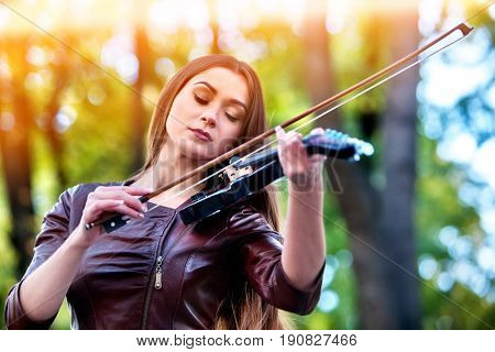 Woman perform music on violin in park outdoor. Girl performing jazz on city street . Spring outside with green tree . Inspired violinist's nature. Sun backlight on background.