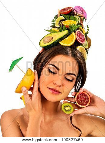 Girl drinking fruit cocktail on summer party. Woman with fresh fruits hairstyle and bare back hold halves of grapefruit with cocktail umbrella. Female enjoys citrus. Concept of drink bar on isolated.