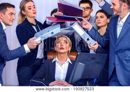 Mad business people office. Team people are unhappy with their leader. Intern woman manager does not cope with his duties. Crazy crowd in stress throw up their chief's papers. Documents for signature.