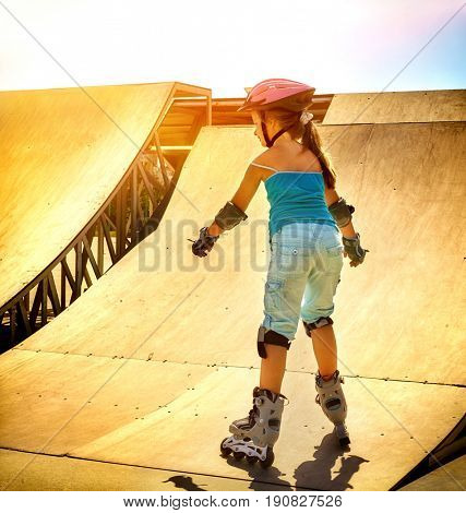 Girl riding on roller skates in skatepark. Backlit on background. View from back of kid. Therapeutic exercise for slimming children. Color tone.