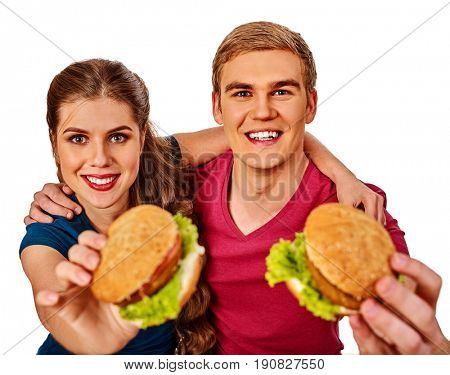Couple eating fast food. Man and woman eat hamburger with ham . Friends holding two burder junk on white background isolated. Loving couple prefers fast food to homemade dinner.
