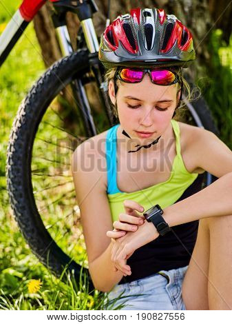 Woman traveling bicycle in summer park. Bicyclist girl watch on smart watch. Girl counts pulse after sport training. Kid is resting on nature at weekend. Girl is waiting for her friends.