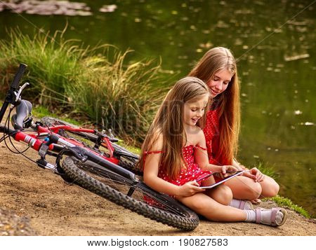 Bikes cycling kids. Girl recreation near bicycle into park. Children watch tablet pc. Girl in ecotourism. Older sister shows younger new game on tablet sitting on river bank near water.