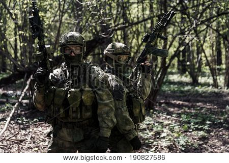 Portrait of soldiers with arms in full grown in woods during day