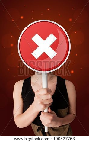 Casual young woman holding round red sign with white cross