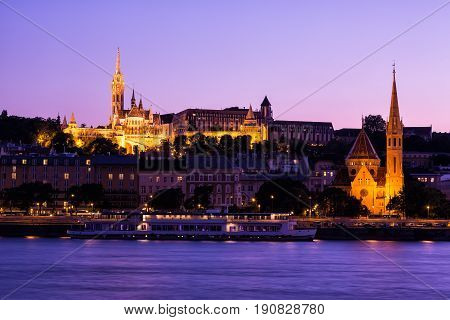 The gothical Matthias church, in the Buda district near the Fisherman's Bastion at sunset with sightseeing ship.