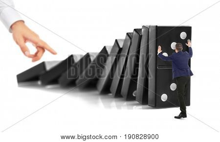 Male hand pushing huge dominoes and man trying to stop their falling on white background. Leadership concept