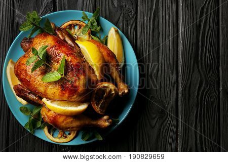 Homemade baked chicken with lemon and mint on wooden background