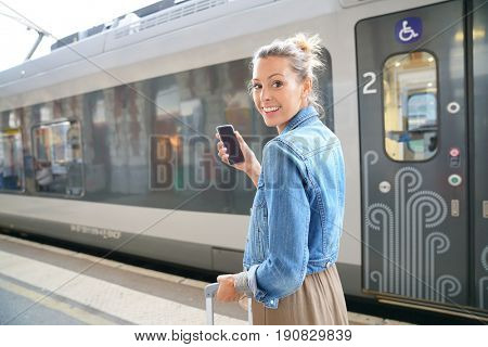 Young trendy woman using smartphone at the train station