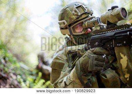 Man in camouflage looks at sight of machine gun in forest ravine