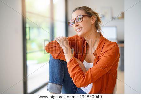 Happy trendy girl sitting on chair in mordern house