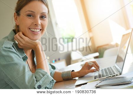 Trendy girl working from home on laptop