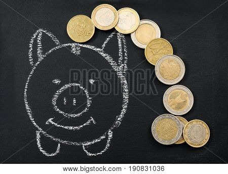 Blackboard with image of piggy bank and coins