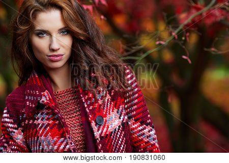 Portrait of beautiful brunette girl walking the park. Smiling. Warm sunny weather. Outdoors