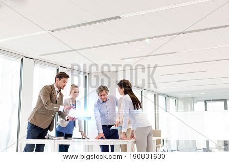 Team of business people having discussion at table in new office