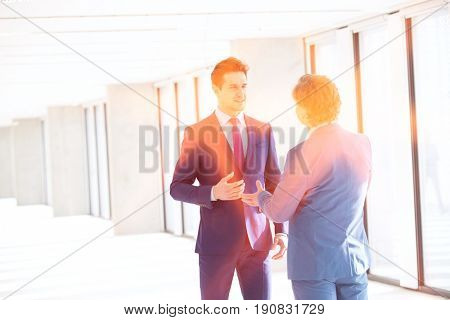 Young businessman talking with male colleague in new office